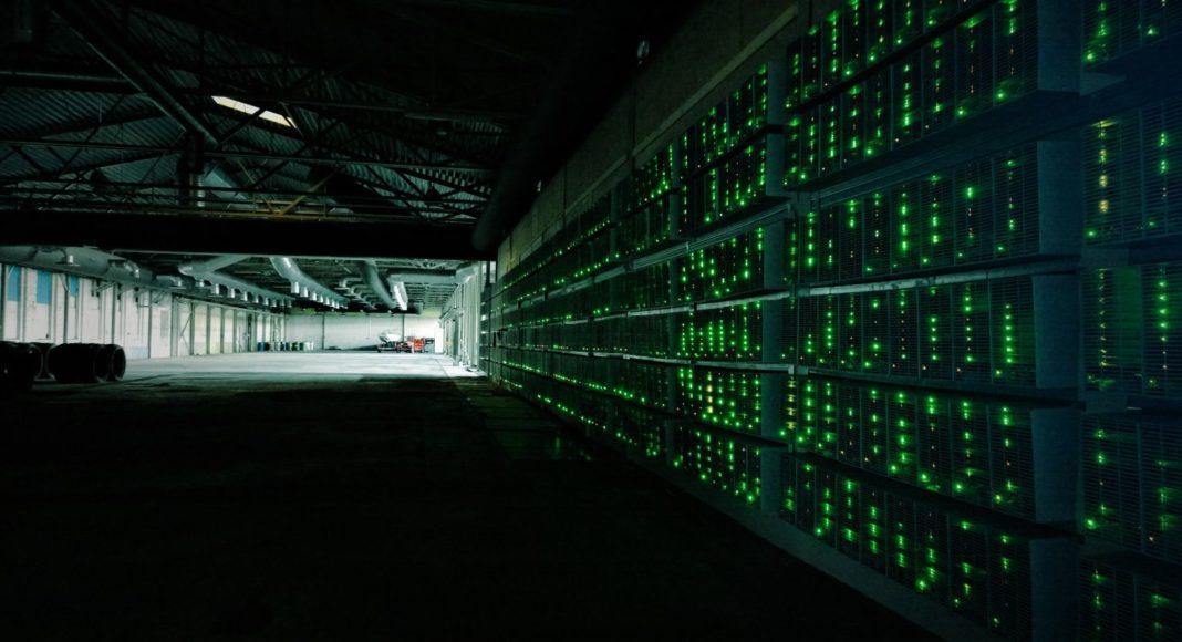 Bitcoin mining machines in a dark hangar, with small green lights.