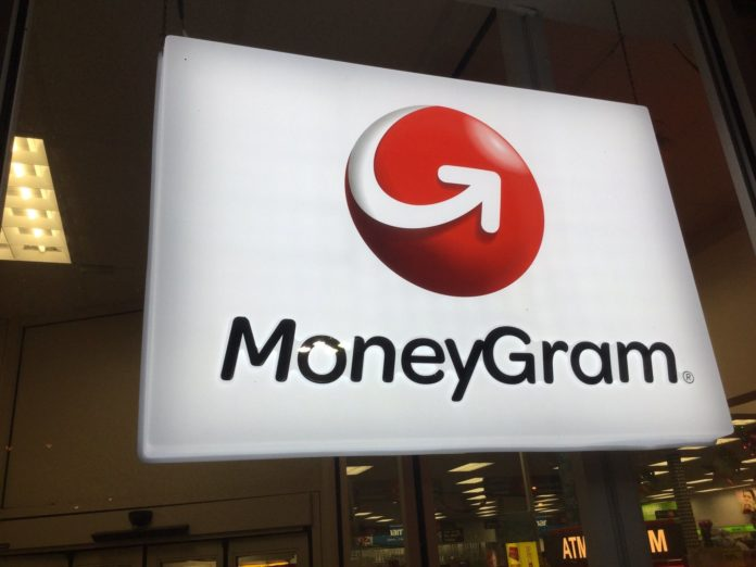 Glowing MoneyGram sign hanging from the ceiling, with an ATM behind it.
