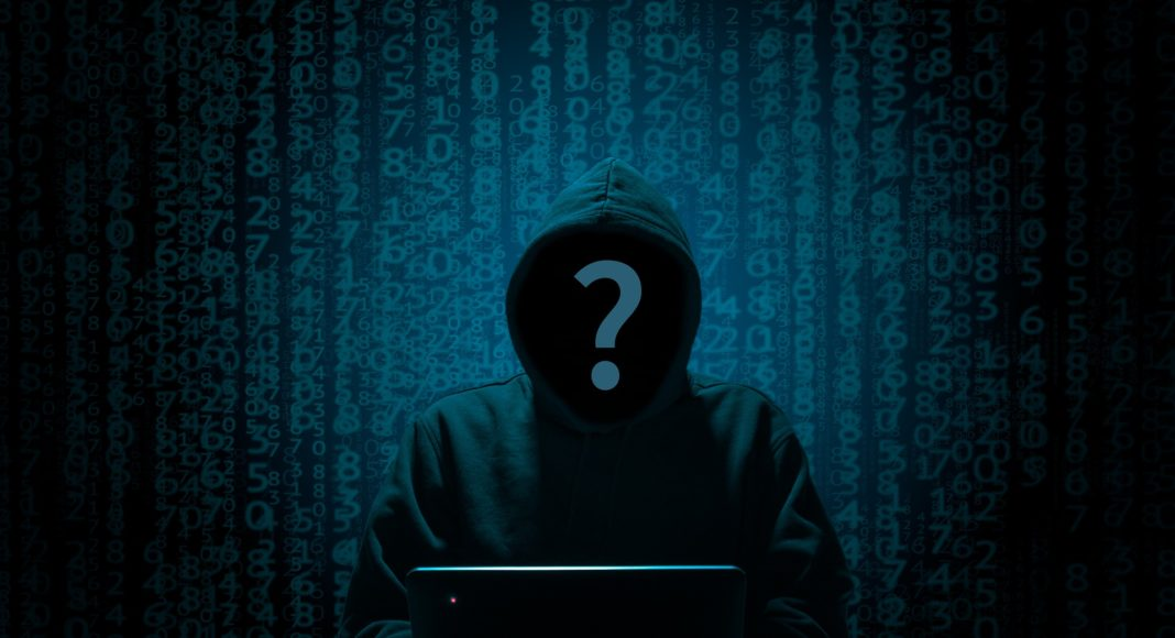 Hacker sitting in front of a laptop, while numbers appear behind him.