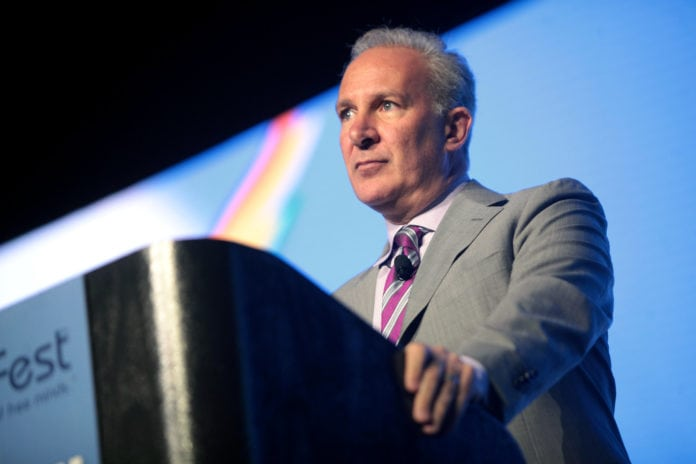 Peter Schiff speaking to the audience behind a desk, wearing a suit and a purple tie.