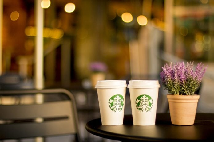 Two starbucks coffee cup on a table, next to a lavender in a flowerpot.
