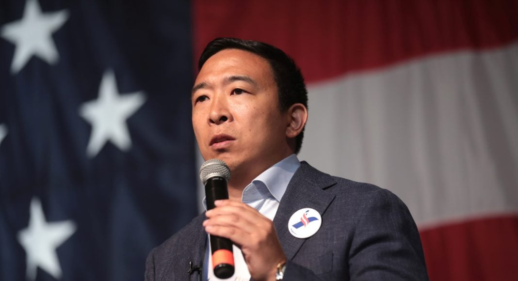 Andrew Yang standing in front of the US flag, with a microphone.