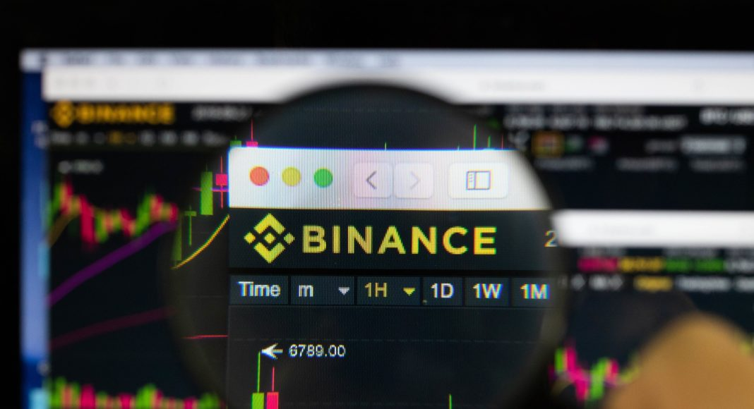 Binance logo on a monitor, looked through a magnifying glass.